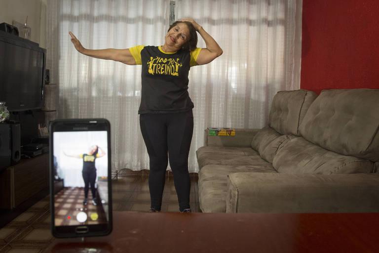 A educadora física Teresinha Alves de Jesus, de 66 anos, ensina uma forma de alongamento de pescoço na sala de sua casa, diante de um celular. Ela grava vídeos com aulas de dança e alongamento e enviando para suas alunas, a maioria com mais de 60 anos