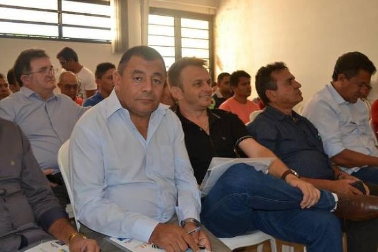 De camisa azul de manga cumprida, Antônio Felícia aparece em sala com janela e porta ao fundo. Ele está sentado com as mãos sobre o colo.