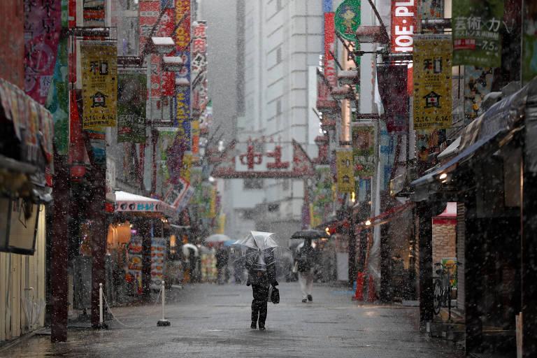 Homem caminha por rua quase vazia em Tóquio