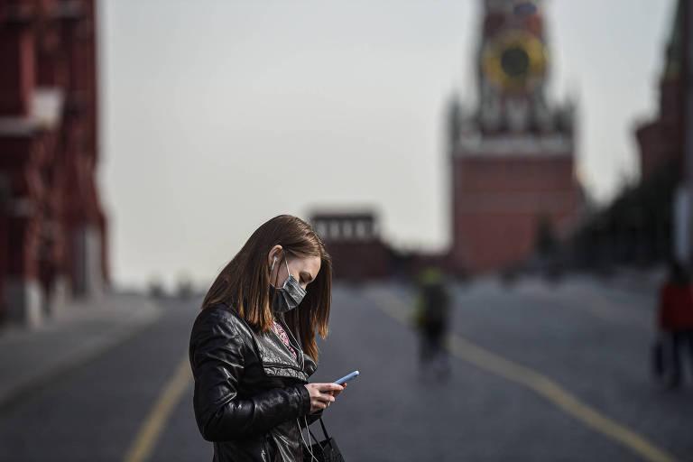 Mulher de máscara utiliza o celular