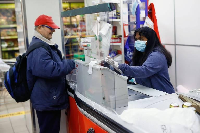 Funcionária usa proteção facial em supermercado em Barcelona