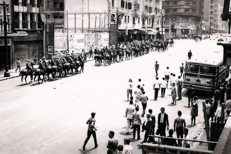Cavalaria militar ao lado de pequena aglomeração de pessoas
