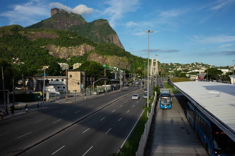 Um ônibus de BRT chega à estação Jardim Oceânico, enquanto poucos carros passam na avenida ao lado