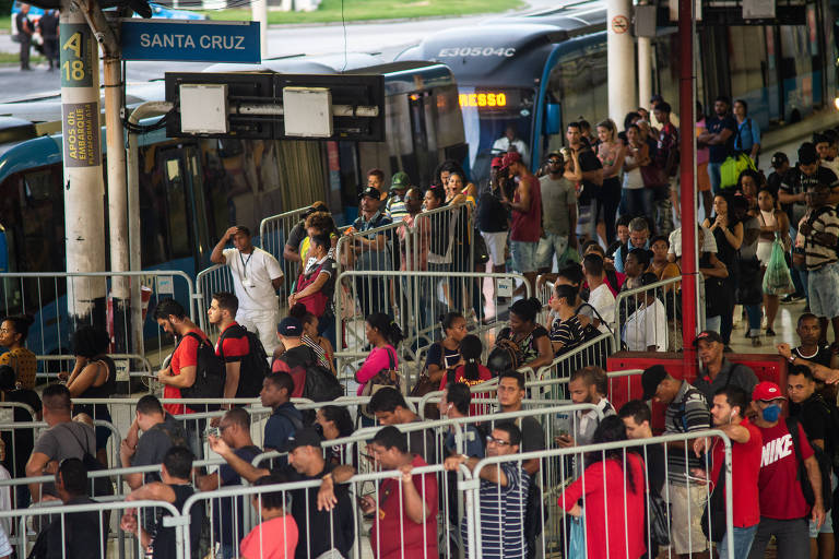 Multidão de pessoas em várias filas longas, separadas por cavaletes de metal, aguardam na estação de BRT do terminal Alvorada