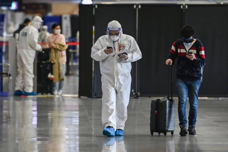Membro da equipe de segurança do aeroporto de Xangai, com roupas de proteção, acompanha passageiro