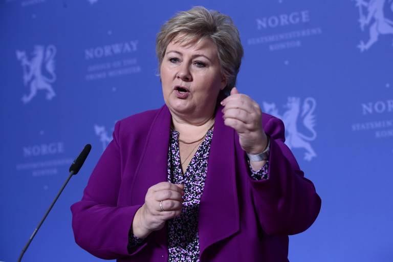 Usando terno roxo, na frente de um fundo azul, a primeira ministra fala ao microfone e gesticula