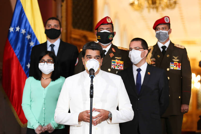 Maduro está em pé, com máscara e roupa branca, em frente a um microfone preto. Há dois seguranças de terno, uma assessora de casaco verde-claro, e dois militares atrás dele. A bandeira venezuelana também está ao lado.