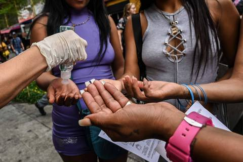 An activist shows to sex workers how to apply hand sanitizer during an awareness campaign to promote safe measures against the spread of the new Coronavirus, COVID-19 in Medellin, Colombia on March 19, 2020. (Photo by JOAQUIN SARMIENTO / AFP)