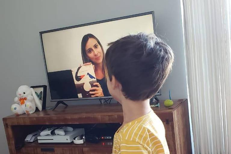 Menino assiste vídeo com atividades escolares