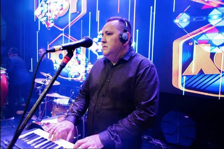 Homem vestido com roupas pretas toca um teclado e está na frente de um microfone