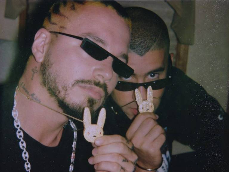 dois cantores com óculos escuros segurando colar