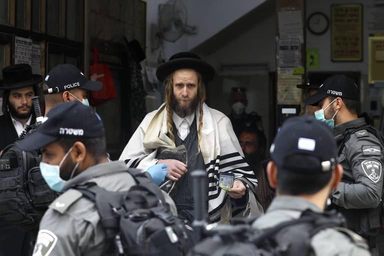 Membros das forças de segurança com luvas e máscaras em sinagoga em Jerusalém