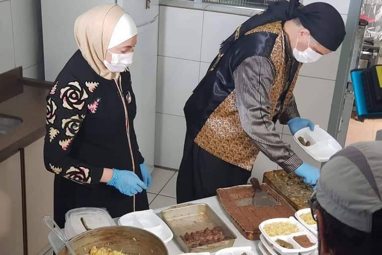 O sírio Talal Al-Tinawi com a mulher, Ghazal, preparando as marmitas para doação
