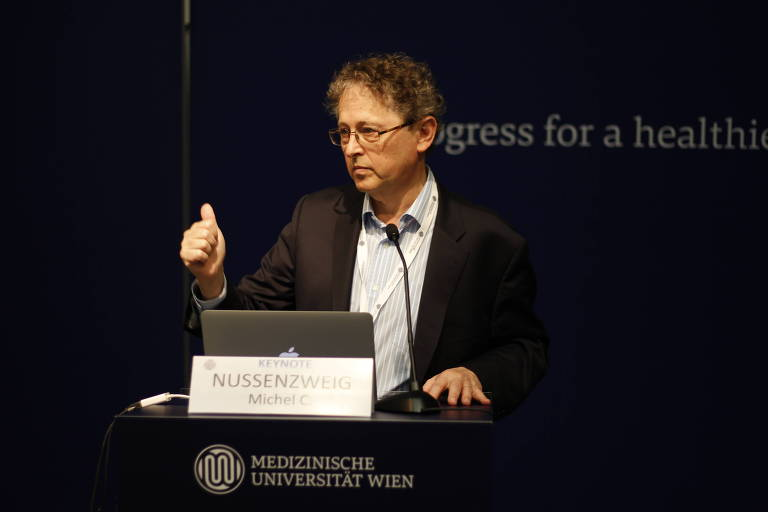 Michel Nussenzweig em palestra na YSA (Young Scientist Association) sobre a dificuldade de criar vacina contra HIV; pesquisador brasileiro lidera estudo nos EUA sobre uso de anticorpos contra coronavírus; o médico é um homem de meia-idade, grisalho e de óculos, com cabelos encaracolados, que veste um blazer escuro sobre uma camisa listrada sem gravata e fala de pé num púlpito