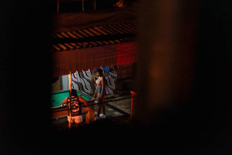 em um bar, ao redor de uma mesa de sinuca, um homem e uma mulher jogam