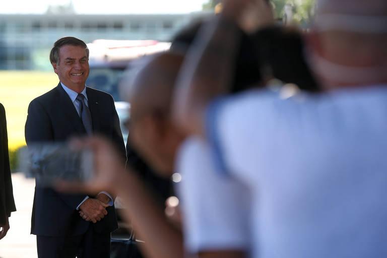 O presidente Jair Bolsonaro cumprimenta apoiadores na saída do Palácio da Alvorada