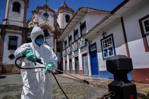 A member of a cleaning crew disinfects the streets around the Basilica of Our Lady of Pilar in Ouro Preto, Minas Gerais state, Brazil, on March 31, 2020, against the new coronavirus, COVID-19. (Photo by DOUGLAS MAGNO / AFP)