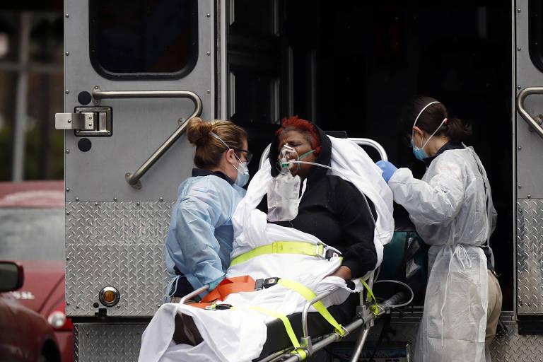 Com equipamentos de proteção, equipe médica coloca paceinte dentro de ambulância em Nova York, em meio à pandemia de coronavírus