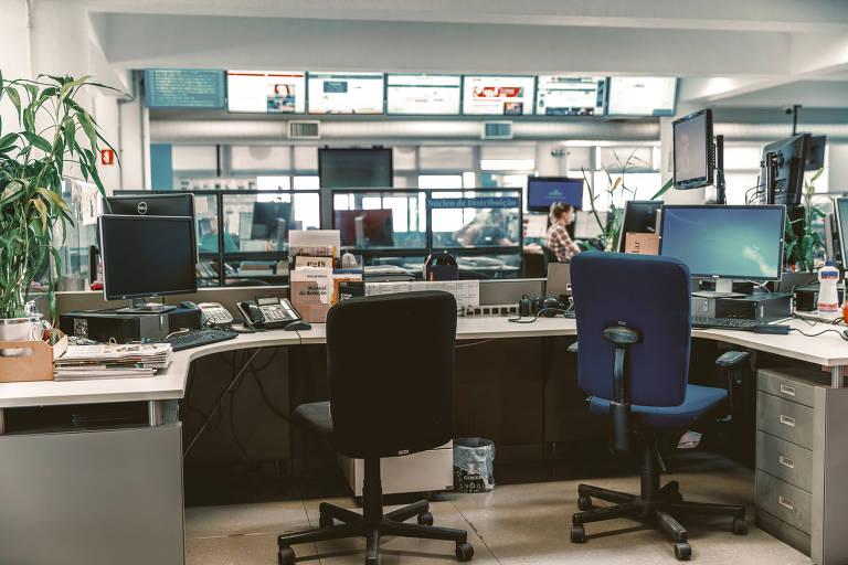 Duas cadeiras vazias de costas, e televisões ao fundo, com outras mesas vazias