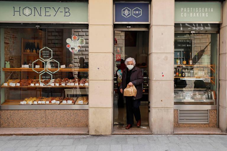 Idosa, de cabelos brancos, usa mascara branca e roupas pretas enquanto sai da porta de uma loja. As paredes da loja são marrom-claro e as vitrines tem vidros expondo doces e alimentos. Há adesivos brancos nos vidros