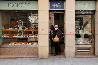 Elderly woman wears a protective face mask as she carries a bag with food products in Barcelona