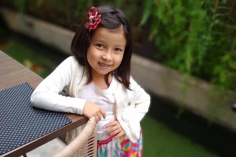 Lara Yumi Mita Coercio, 7 anos, usa casaco branco, tem cabelos lisos pelo ombro, origem nipônica e saia colorida com cores quentes
