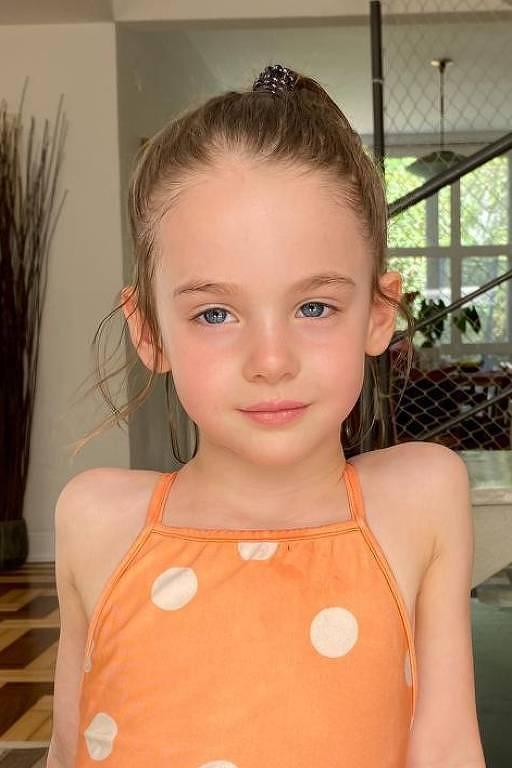 Cecília está de cabelos presos num rabo de cavalo e camiseta laranja na sala de sua casa
