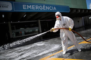 A member of the armed forces disinfects the entrance of a hospital during the coronavirus disease (COVID-19) outbreak in Brasilia