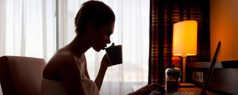 Young woman sitting at laptop in hotel room ORG XMIT: IPTC last updated on 14/10/14 ***PARCEIRO FOLHAPRESS - FOTO COM CUSTO E CRÉDITO OBRIGATÓRIO. PARA OBTER ESTA IMAGEM EM ALTA, ENVIE PEDIDO PARA PESQUISA@FOLHAPRESS.COM.BR***