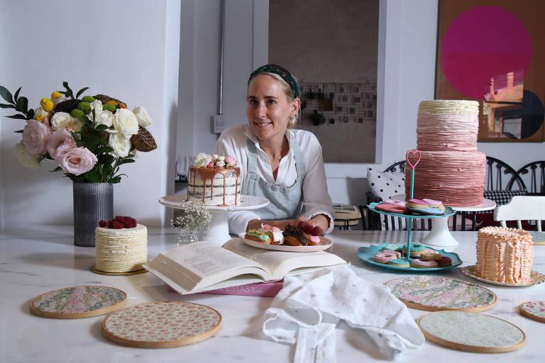 Mulher sentada à mesa com bolos decorados, arranjo de flores e livro