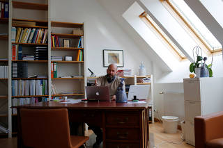 Self-employed psychologist Neuwirth gestures inside his office during the coronavirus disease (COVID-19) outbreak in Vienna