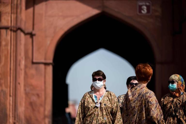 No canto da foto, aparecem quatro mulheres. Duas delas usam máscara, uma está de costas. Elas vestem túnicas na cor marrom e óculos. Ao fundo, há uma grande entrada, em estilo árabe, em um edifício marrom