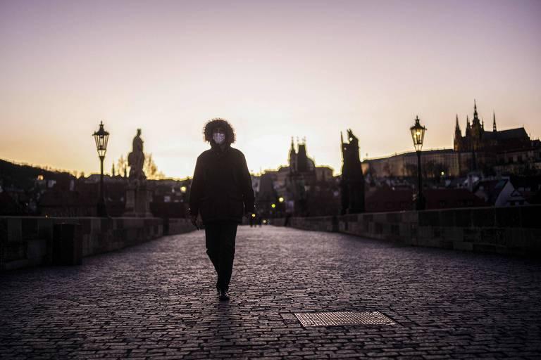 Homem anda por ponte de Praga, na República Tcheca, país que reduziu atividades em meio à pandemia