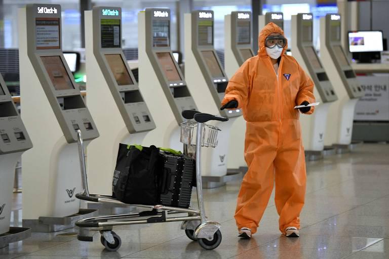 Passageiro usa máscara e traje protetor para fazer check-in no aeroporto internacional Incheon, em Seul, na Coreia do Sul
