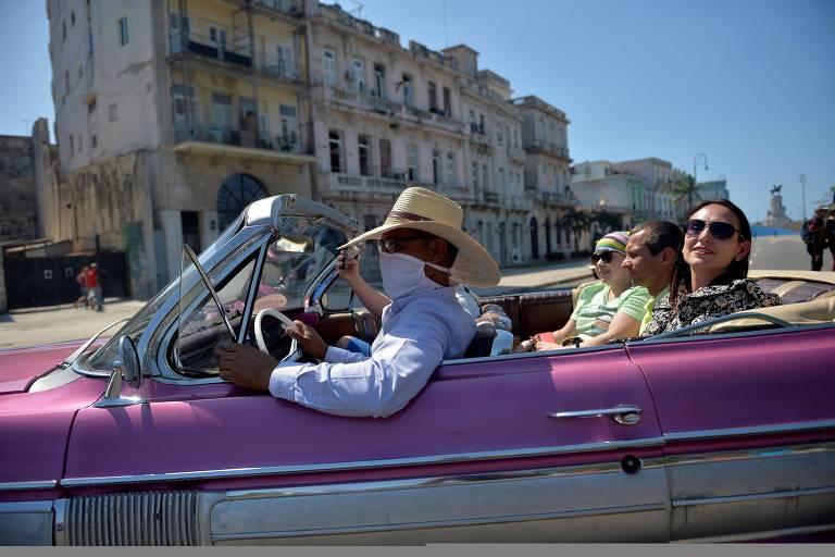 Três pessoas em carro rosa conversível, o motorista usa chapéu e uma máscara cirúrgica