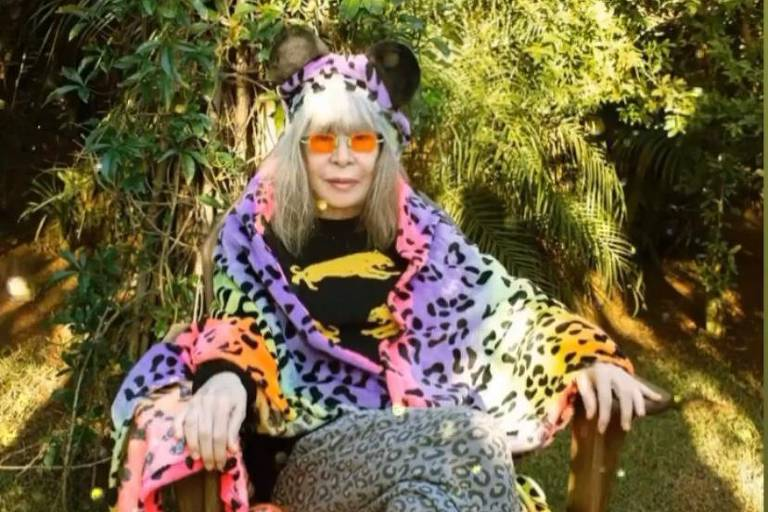 """Rita Lee sentada em cadeira que lembra trono, com uma manta colorida sobre os ombros e com adesivos virtuais de """"Fique em Casa"""" (""""Stay Home"""", no original)"""