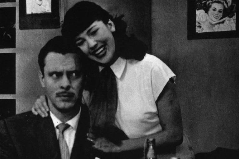 """Homem e mulher se abraçam de lado. Mulher sorri e homem faz """"cara séria"""""""
