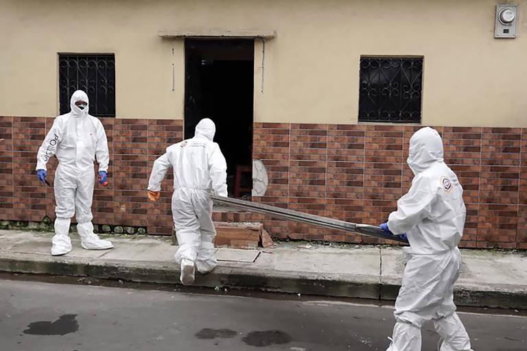 Policiais e peritos, com roupas de proteção, retiram corpo de vítima da Covid-19 de uma casa em Guayaquil