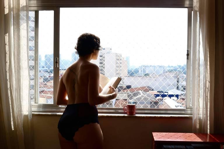 Mulher seminua olha para a janela com um livro
