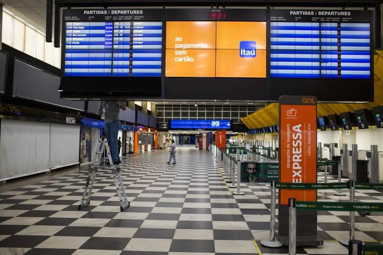 Saguão do aeroporto, vazio. Ao fundo, painéis mostram apenas sete voos previstos