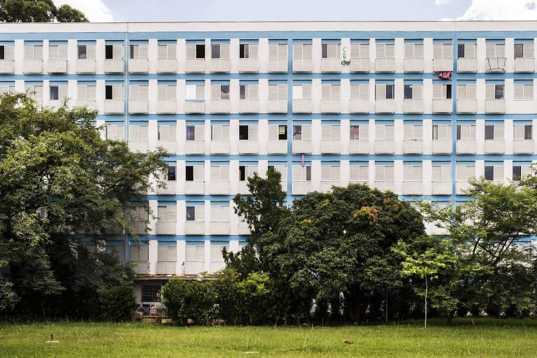 Vista de um dos prédios do Conjunto Residencial da USP; na foto vemos um prédio cuja fachada é composta de muitas janelinhas brancas, com estruturas verticais e horizontais em azul, que dá para um gramado e árvores