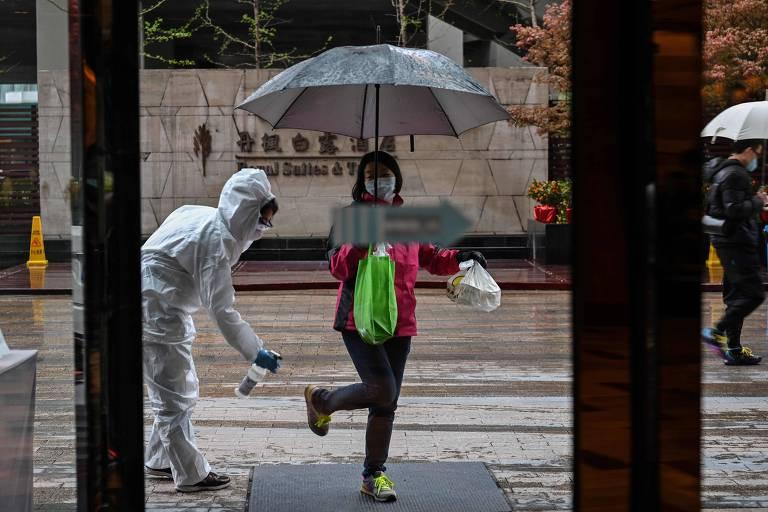 Homem com roupa protetiva branca cobrindo todo o corpo passa desinfetando no tênis de uma mulher, que está de máscara, luvas, carrega um guarda-chuva, uma sacola verde e outra branca, está de casaco rosa e calças pretas.