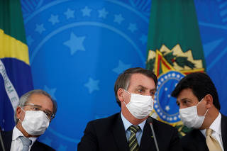 Brazil's President Bolsonaro, Minister of Health Mandetta and Economy Minister Guedes attend a news conference to announce measures to curb the spread of the coronavirus disease (COVID-19) in Brasilia