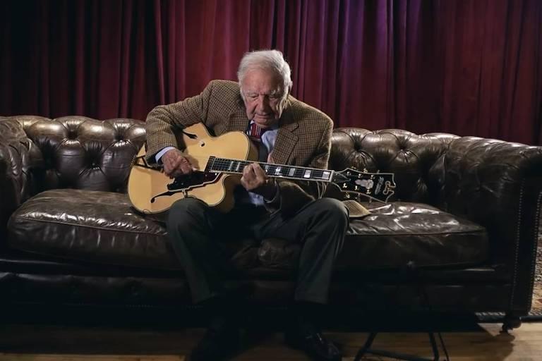 idoso tocando guitarra em um sofá