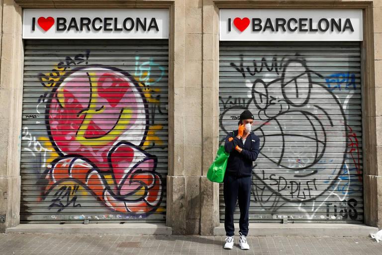 """homem de roupas pretas e mascara branca, carrega sacola ver e está parado em frente a duas portas de ferro fechadas e pichadas. Em cima das portas, há placas com os dizeres: """"I love Barcelona"""""""