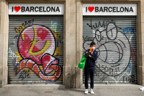 A man wearing a mask speaks by mobile in front of a closed shop during an outbreak of coronavirus disease (COVID-19) in Barcelona, Spain, March 18, 2020. REUTERS/ Albert Gea ORG XMIT: GGG-BAR004