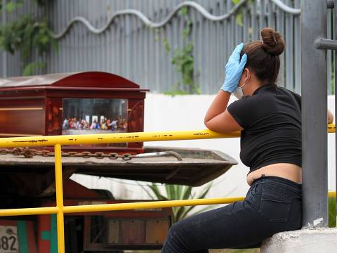 A woman wearing a face mask and gloves mourns as she waits for the corpse of a relative outside a hospital in Guayaquil, Ecuador on April 1, 2020. - Residents of Guayaquil, in Ecuador's southwest, express outrage over the way the government has responded to the numerous deaths related to the novel coronavirus, COVID-19, saying there are many more deaths than are being reported and that bodies are being left in homes for days without being picked up. Ecuador marked its highest daily increase in deaths and new cases of coronavirus on Sunday, with the total reaching 14 dead and 789 infected, authorities had said. (Photo by Enrique Ortiz / AFP)