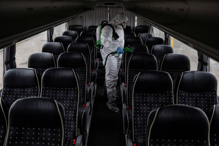 Homem com traje de proteção desinfeta ônibus em Varsóvia na Polônia