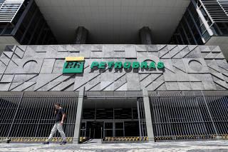FILE PHOTO: A man walks in front of the headquarters of Petroleo Brasileiro S.A. (Petrobas) in Rio de Janeiro
