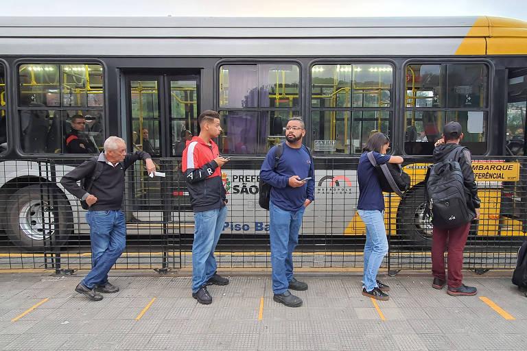 Passageiros embarcam em ônibus no Terminal Cidade Tiradentes, na zona leste de São Paulo, onde o chão foi pintado para os usuários manterem distância